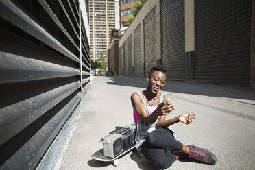 Smiling young woman taking selfie next to skateboard and boom box in urban alley - HEROF31777