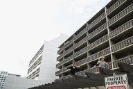 Young man free running below urban apartment buildings - HEROF31780