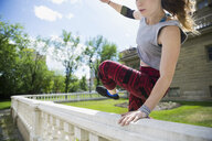 Young woman doing parkour jumping over railing - HEROF31783