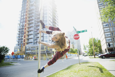Young woman doing parkour on pole in urban street - HEROF31786