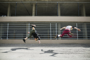 Young man doing parkour against fence in urban alley - HEROF31792
