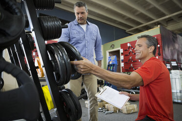 Worker with clipboard showing man plate weights in home gym equipment store - HEROF31840