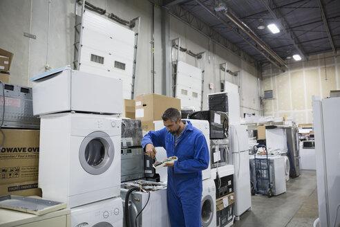 Worker repairing appliances in workshop - HEROF31849