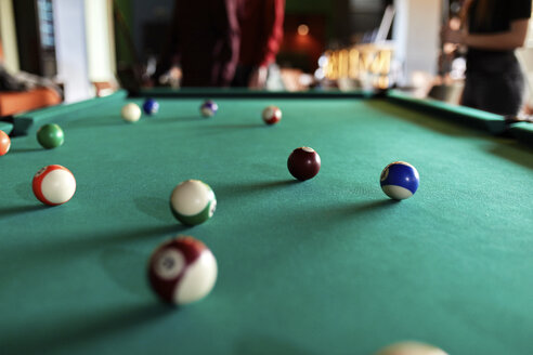 Billiard balls on table with people in background - ZEDF02015