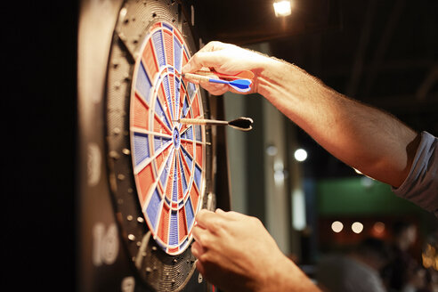 Close-up of man taking out darts from electronic dartboard - ZEDF02021