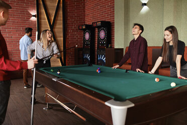 Happy friends playing billiards together - ZEDF02024