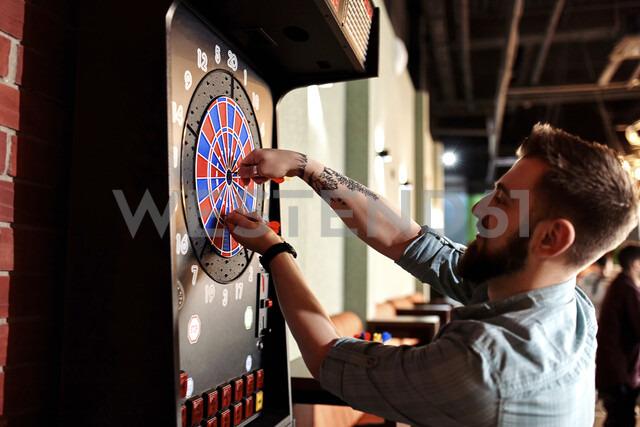 Man taking out darts from electronic dartboard - ZEDF02027 - Zeljko Dangubic/Westend61