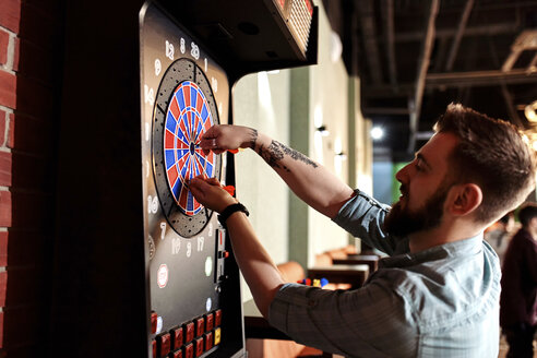 Man taking out darts from electronic dartboard - ZEDF02027