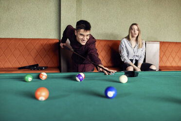 Man playing billiards watched by girlfriend - ZEDF02036