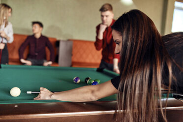 Young woman playing billiards with friends - ZEDF02039
