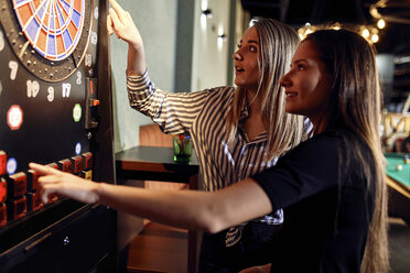 Two women playing darts setting electronic dartboard - ZEDF02057