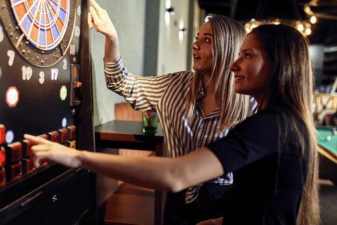 Two women playing darts setting electronic dartboard - ZEDF02057