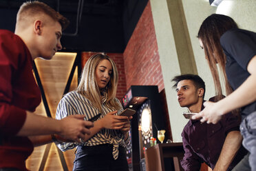 Friends with smartphones socializing in a bar - ZEDF02069