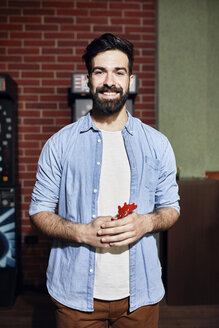Portrait of smiling man holding darts - ZEDF02072
