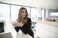 Businesswoman drinking coffee in office - HEROF31872