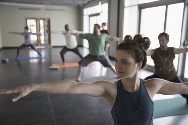 Woman practicing yoga warrior 2 pose in yoga class studio - HEROF32103