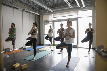 Yoga class practicing tree pose in studio - HEROF32109