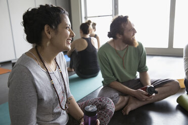 Smiling friends with water bottles talking on yoga mats in yoga class - HEROF32112