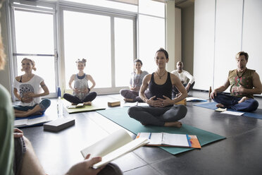 Yoga class with journals practicing breathing with hands on stomachs in yoga class studio - HEROF32115