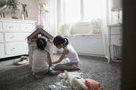 Sisters playing with dollhouse on carpet in bedroom - HEROF32136
