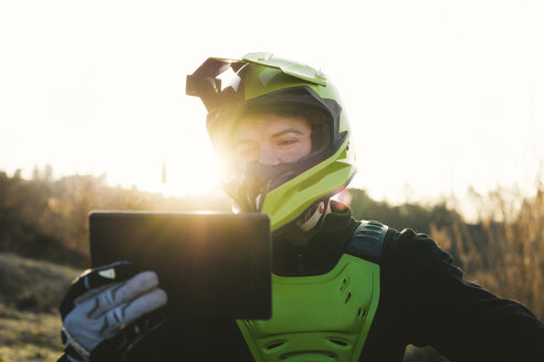 Portrait of motocross driver looking at tablet at sunset - FBAF00338