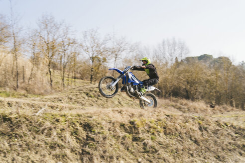 Motocross driver riding on circuit doing a wheelie - FBAF00356