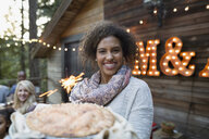 Portrait smiling woman serving fresh baked pie with sparkler on cabin balcony - HEROF32167