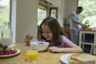 Smiling girl eating breakfast at kitchen table - HEROF32170