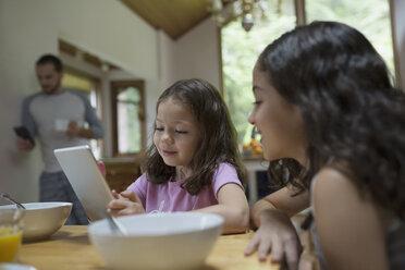 Sisters using digital tablet at breakfast table - HEROF32173