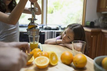 Sisters juicing oranges in kitchen - HEROF32176