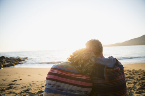 Serene affectionate couple wrapped in blanket looking at sunset ocean view - HEROF32212
