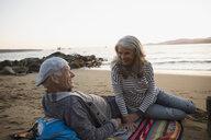 Senior couple relaxing on a blanket on sunset beach - HEROF32221