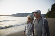 Senior couple walking on beach at sunset - HEROF32224