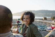 Smiling couple drinking wine enjoying picnic on beach - HEROF32236