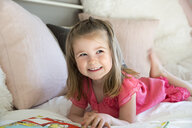 Smiling girl reading book laying on sofa - HEROF32242