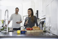 Smiling couple drinking wine and cooking in kitchen - HEROF32245