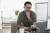 Serious man using laptop and drinking coffee in kitchen - HEROF32248