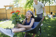 Smiling father pushing daughter with potted flower in backyard - HEROF32257