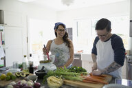Pregnant couple preparing vegetables in kitchen - HEROF32260