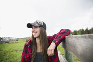 Smiling female cattle rancher leaning on fence looking away - HEROF32272