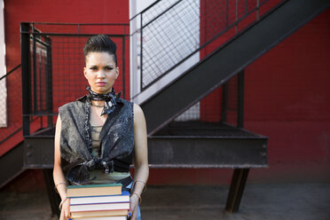 Portrait tough cool young woman holding stack of books near urban stair - HEROF32281