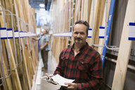Portrait smiling worker with clipboard in home improvement store - HEROF32296