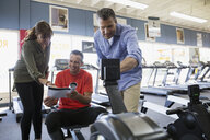 Salesman explaining rowing machine to couple in home gym equipment store - HEROF32311