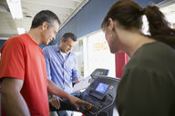 Salesman helping couple shopping for treadmill in home gym equipment store - HEROF32314