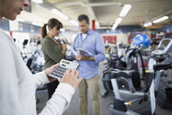 Saleswoman with calculator in home gym equipment store - HEROF32317