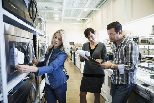 Saleswoman with clipboard helping couple shopping for microwave in appliance store - HEROF32350