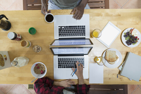 Overhead view couple using laptops at breakfast table - HEROF32359
