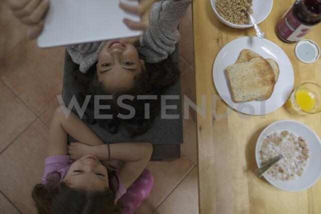 Overhead view sisters using digital tablet at breakfast table - HEROF32365 - Hero Images/Westend61