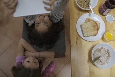 Overhead view sisters using digital tablet at breakfast table - HEROF32365