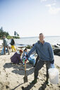Portrait smiling beach cleanup volunteer picking up litter on sunny beach - HEROF32383